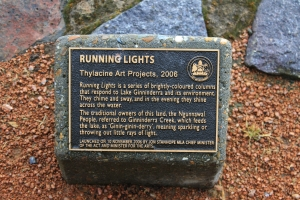 This plaque relates to the colored poles featured on Lake Ginninderra seen in the photo below.